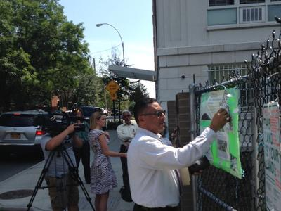 Victor reattaching some signage while Bronx 12 News visits